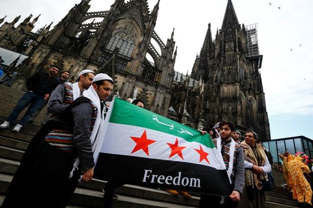 מהגרים מסוריה מחזיקים בדגל שלהם מחוץ לקתדרלה בגרמניה, צילום: רויטרס