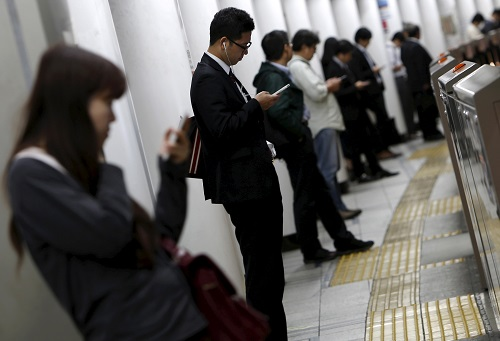 People look at their mobile phones while waiting for a train at a subway station in Tokyo