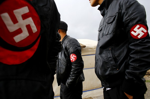 Members of the Mongolian neo-Nazi group Tsagaan Khass stand near a quarry, where they questioned a worker, southwest of Ulan Bator June 23, 2013. The group has rebranded itself as an environmentalist organisation fighting pollution by foreign-owned mines, seeking legitimacy as it sends Swastika-wearing members to check mining permits. Over the past years, ultra-nationalist groups have expanded in the country and among those garnering attention is Tsagaan Khass, which has recently shifted its focus from activities such as attacks on women it accuses of consorting with foreign men to environmental issues, with the stated goal of protecting Mongolia from foreign mining interests. This ultra-nationalist group was founded in the 1990s and currently has 100-plus members. Picture taken June 23, 2013. REUTERS/Carlos Barria (MONGOLIA - Tags: POLITICS ENVIRONMENT BUSINESS SOCIETY EMPLOYMENT) ATTENTION EDITORS: PICTURE 19 OF 25 FOR PACKAGE 'MONGOLIA'S ENVIRONMENTAL NEO-NAZIS'. TO FIND ALL IMAGES SEARCH 'TSAGAAN KHASS' - RTX119T4