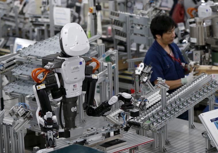 In una fabbrica, un robot umanoide lavora fianco a fianco dei dipendenti alla catena di montaggio. (Photo credit: REUTERS)