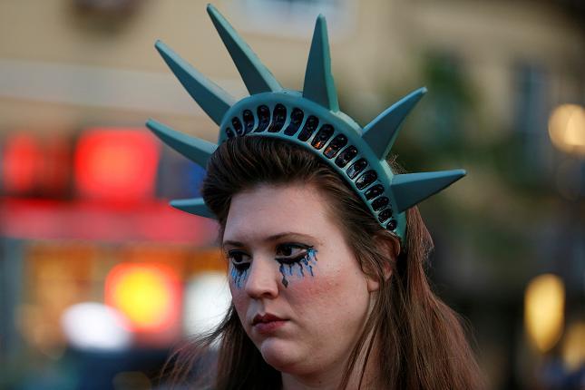 Una manifestante indossa un copricapo raffigurante la corona della Statua della Libertà durante una protesta a San Francisco, California, Stati Uniti dopo l'elezione di Donald Trump come presidente degli Stati Uniti avvenuta il 9 novembre 2016.